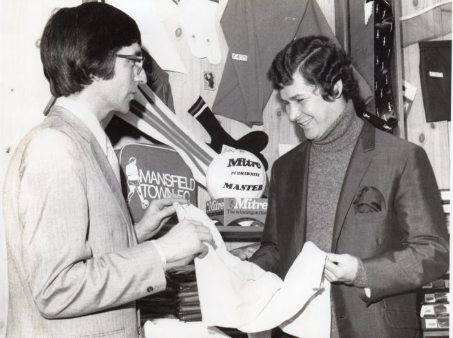 Alan Packer presents a shirt to a Stags player