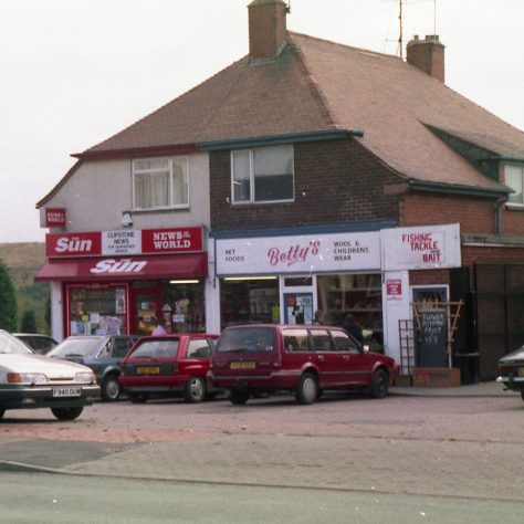 More cars & shops on Mansfield Road. (grassed Pit Tip in background) | Malcolm Marples