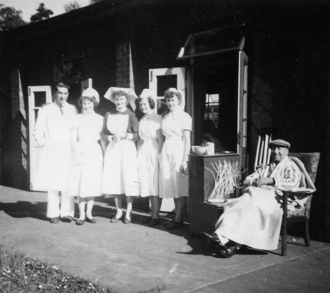 A happy patient with staff outside one of the wards. The patient has cane work (possibly a tray) at the side of him which would have been supplied by the Occupational Therapy Department | Private Collection