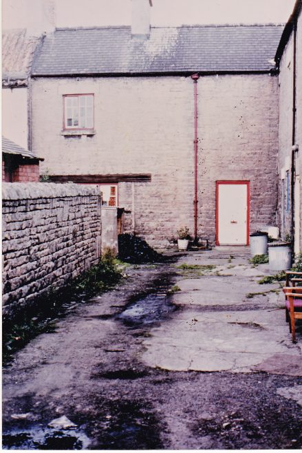 This 1979 image of number 45 Blackgate Yard was taken by Sydney Booth while visiting his mother Agnes 'Dorothy' Cox. The chairs on the right are outside the house then occupied by Dorothy's eldest son George (by her second marriage). Behind the stone wall on the left can just be seen the row of brick toilets for numbers 40, 41, 42, 43, 44 and 45. A fresh load of coal has been delivered for number 45. Also on view are galvanised dustbins and the old doorway to 45, now blocked up. The piece of ground in front of 45 hidden from view was included in the rent. Taken in winter as the puddles are frozen | Glenn Sutcliffe