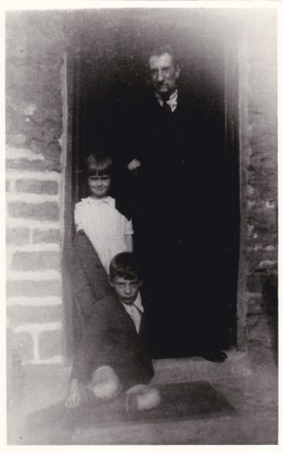 George William Cox 'Cox the painter' with two of his children, Rennie and George in the doorway of 45 Blackgate Yard, 1940. | Glenn Sutcliffe