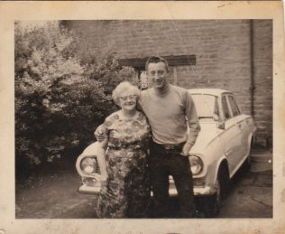 Dorothy Agnes Cox and her youngest child, Rodney proudly showing off his car, possibly the first in Blackgate yard, about 1963. | Glenn Sutcliffe