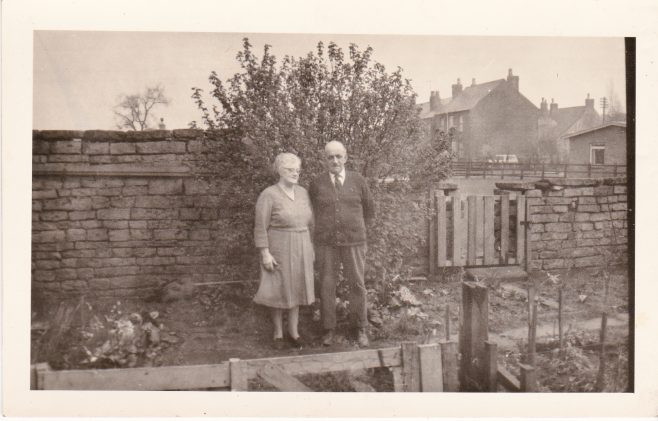 Dollie and David Cooper in the garden of 45 Blackgate Yard. To the right is the way through to the allotments. Out of shot to the right was a pig sty. In distance the roof and gable of the stone farmhouse that once stood on Ley Lane can be seen. | Glenn Sutcliffe