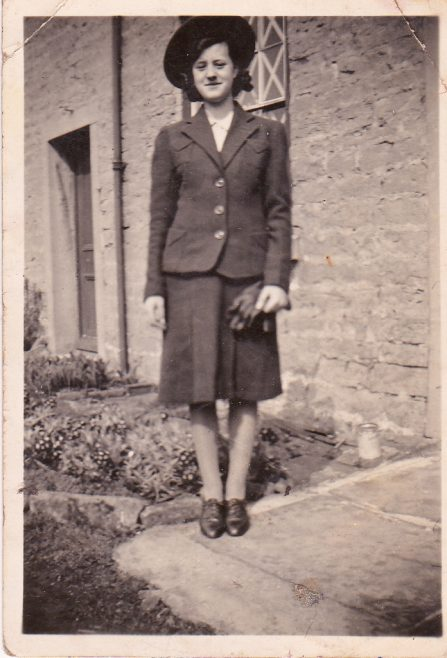 Dollie Cox, eldest daughter of George and Dollie Cox outside one of the houses to the right of the entry to Blackgate Yard. Taken in war time as there is tape across the window panes behind her. | Glenn Sutcliffe